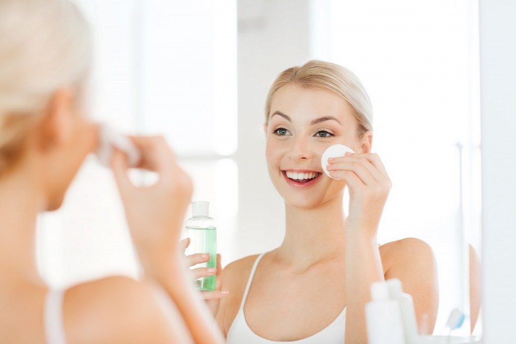 smiling young woman applying skin toner