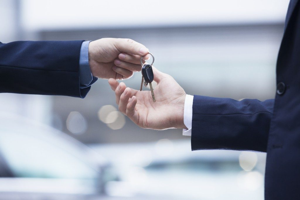 Car rental service handing over the keys for a car to a businessman