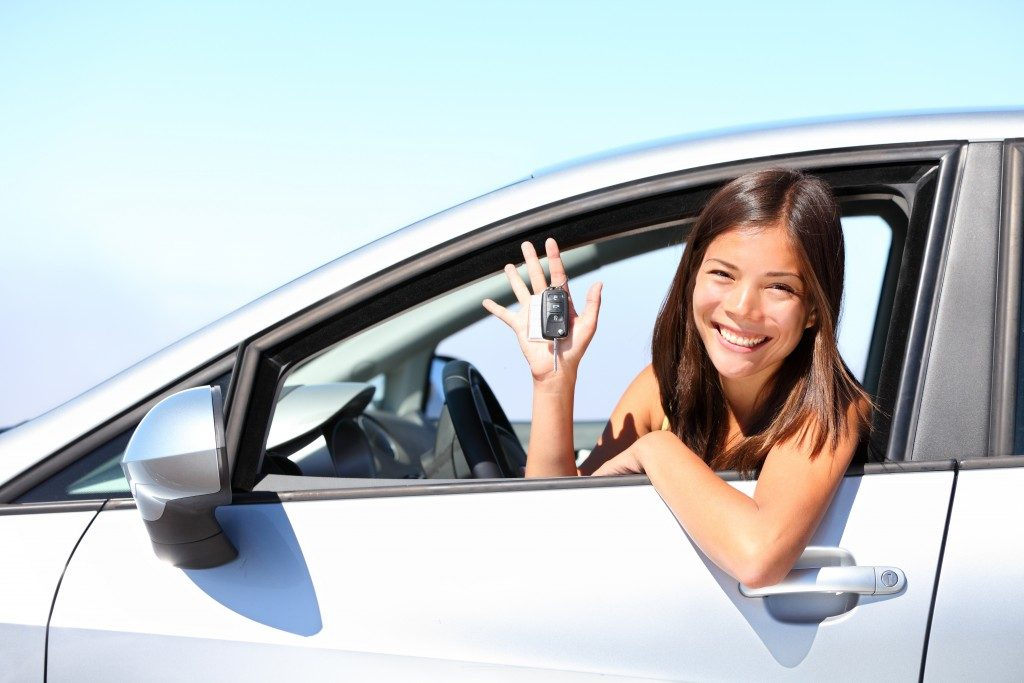 woman smiling inside her rented car