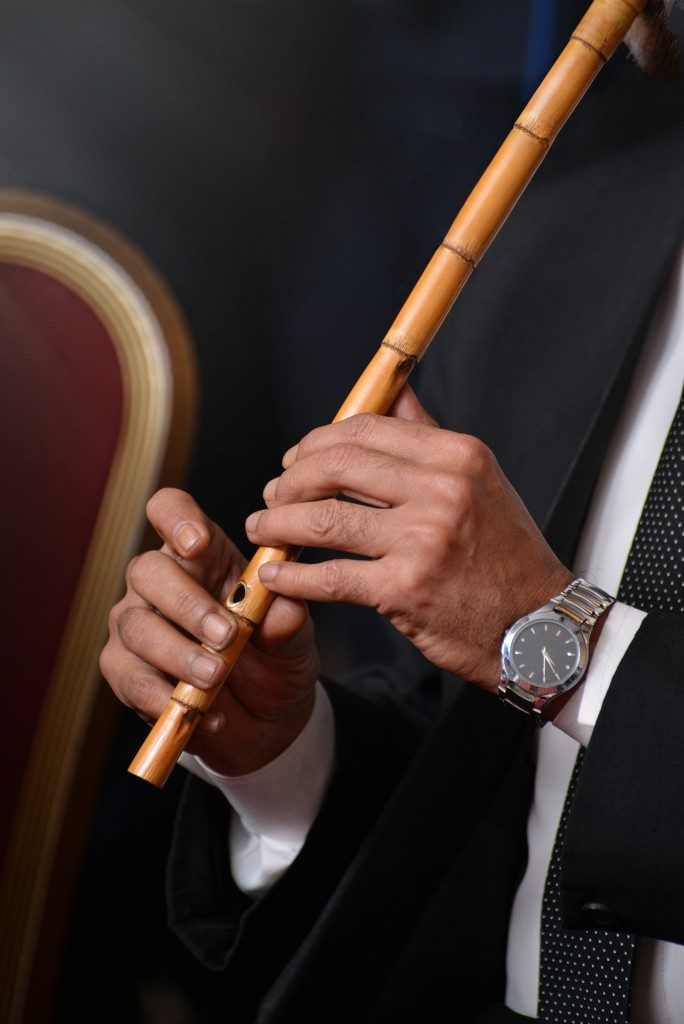 man using a bamboo flute