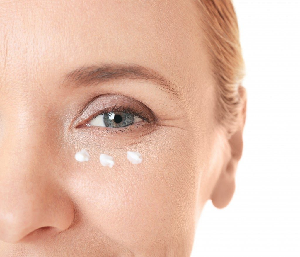 Close up of woman with moisturizer near eye part