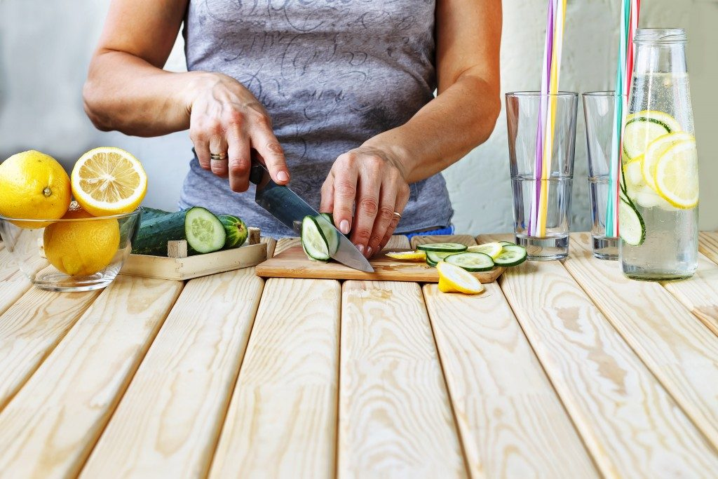 woman cutting up cucumber and lemons