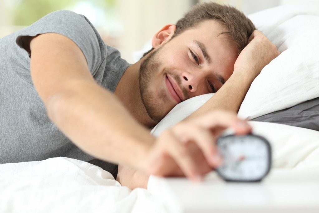 Man stopping the alarm clock