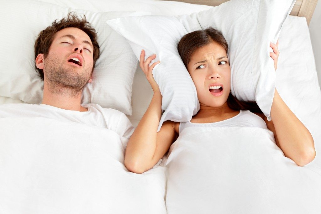 man snoring and woman can not sleep, covering ears with pillow