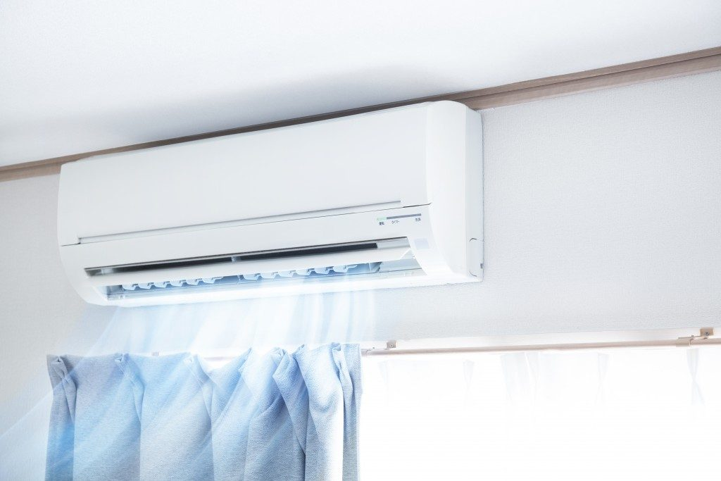 white air conditioner installed above the window of the living room