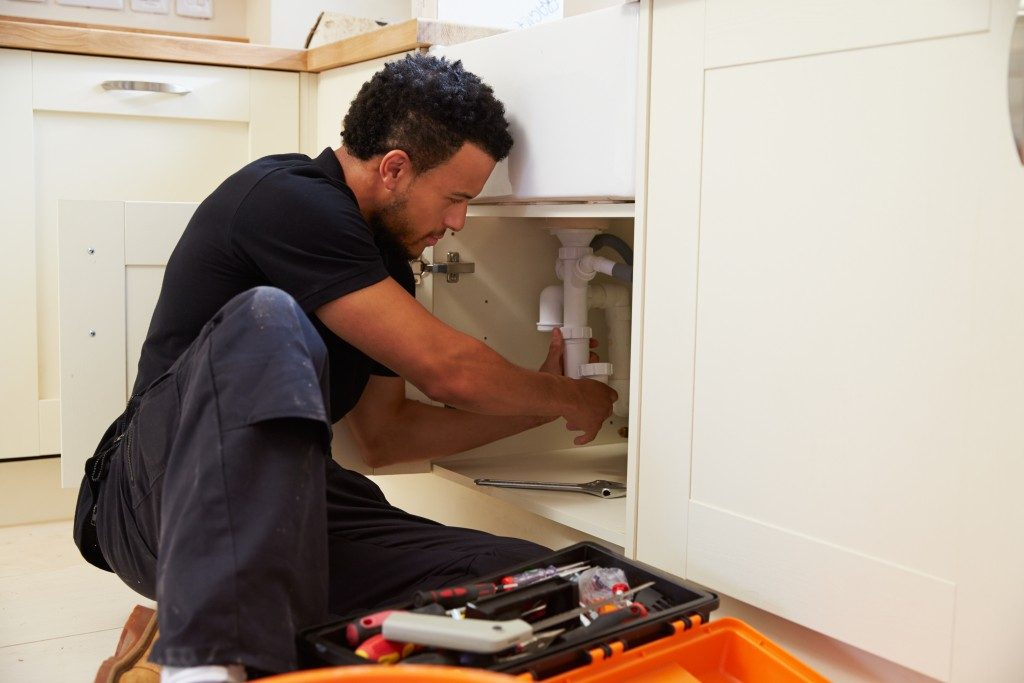 man fixing the plumbing system in the kitchen