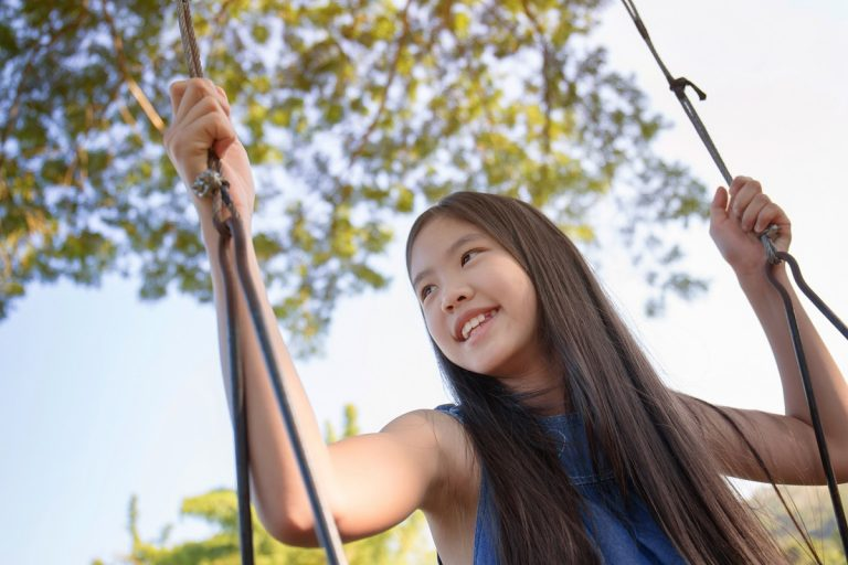 young girl happy playing in the swing