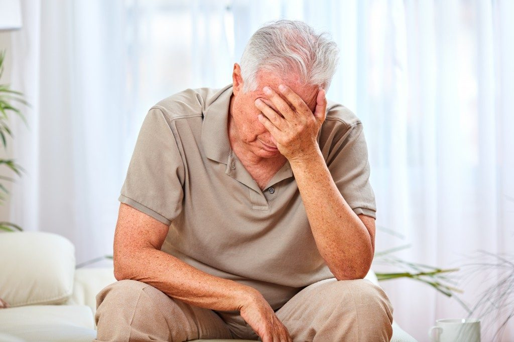elderly man sitting and covering his face, not feeling good