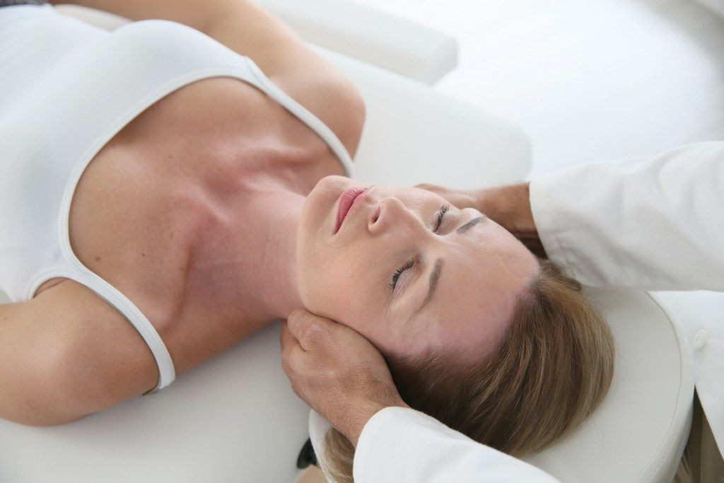 Woman having chiropractic neck adjustment