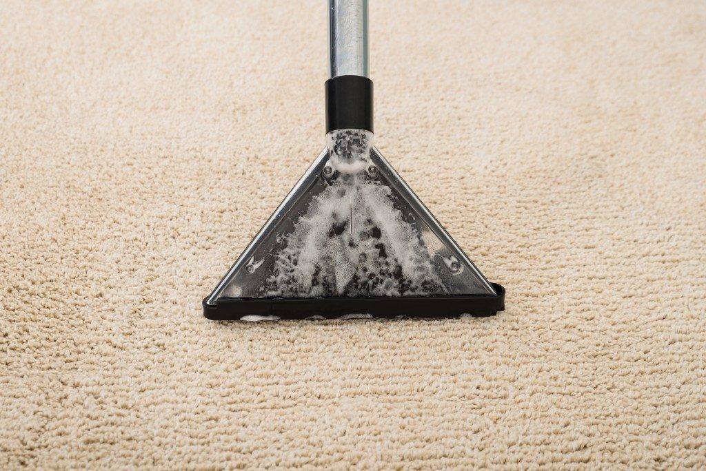 High Angle View Of Electric Vacuum Cleaner Over Carpet With Foam
