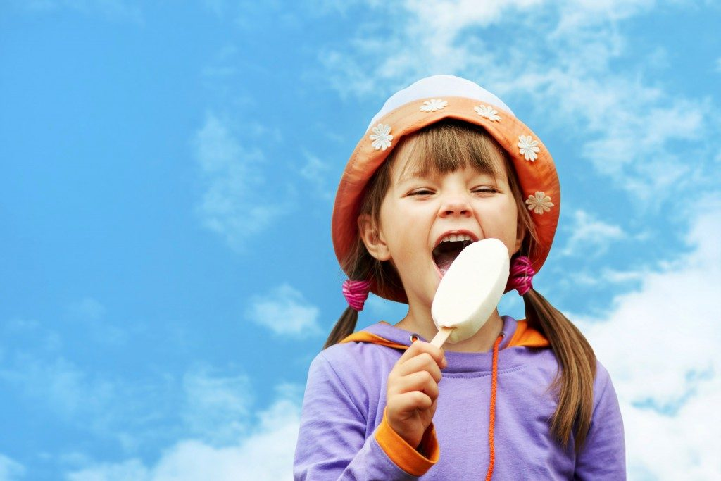 kid happily eating icecream outdoors