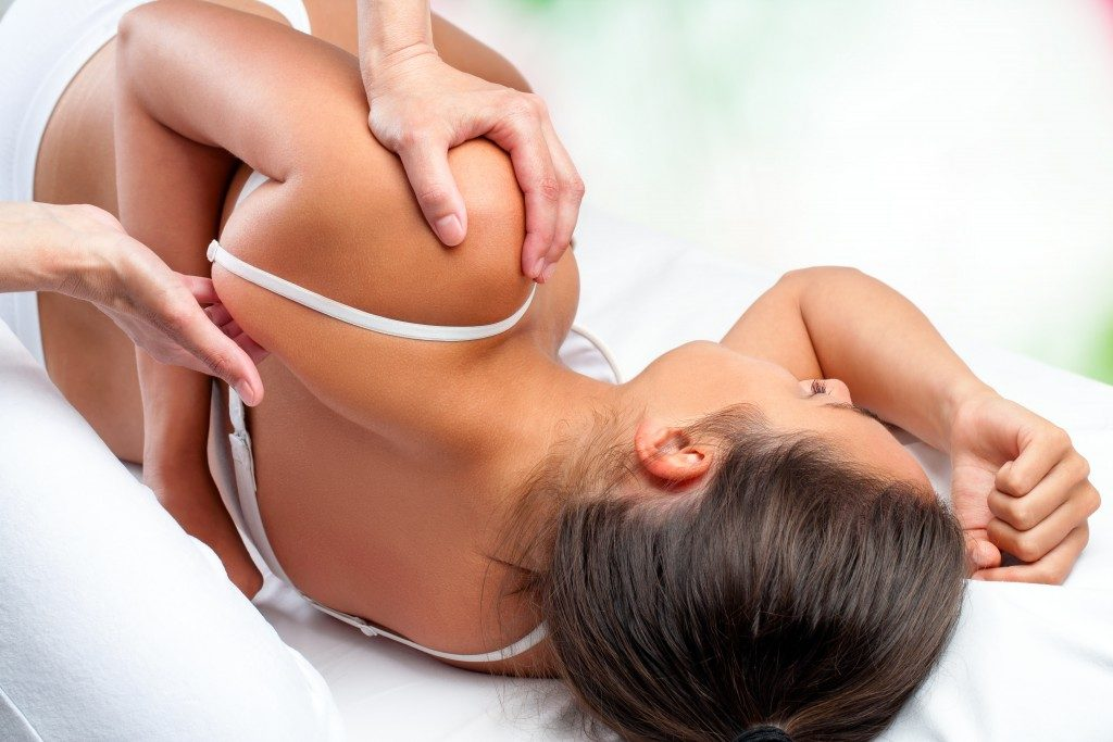 Close up top view of osteopath doing healing treatment on female shoulder blade