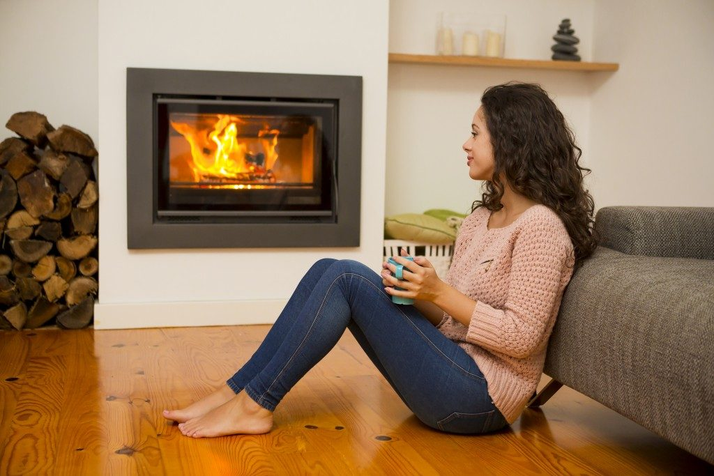 Woman next to a fireplace