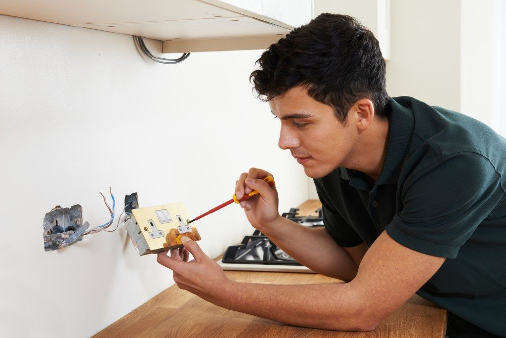 man checking the electrical wiring of his home