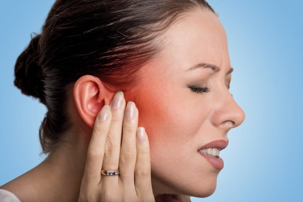 woman suffering from ear pain