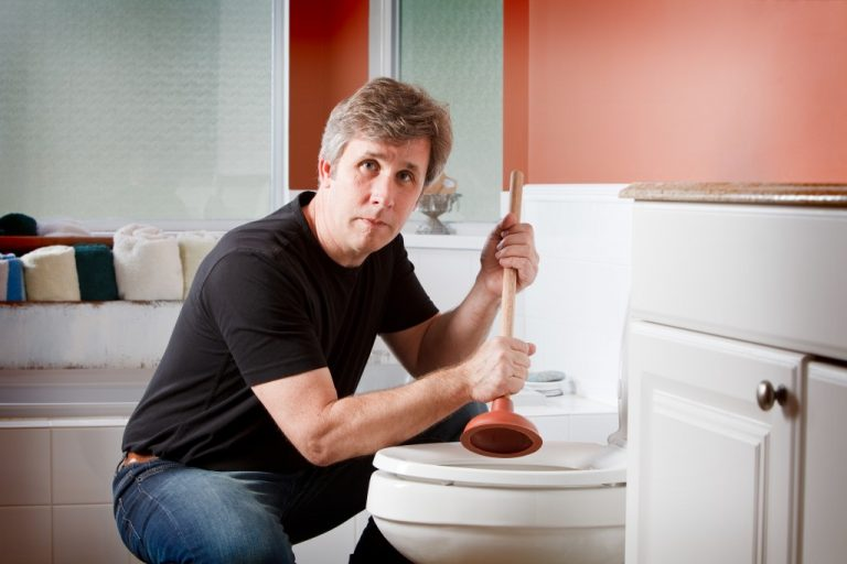 using a plunger to clear a clogged toilet