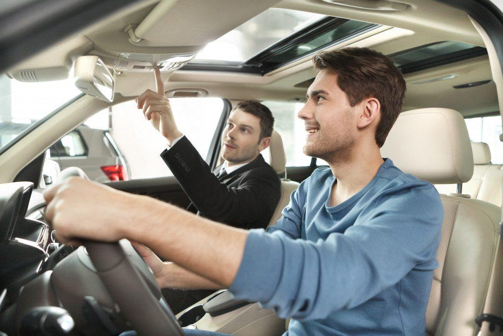 salesman and customer looking at car