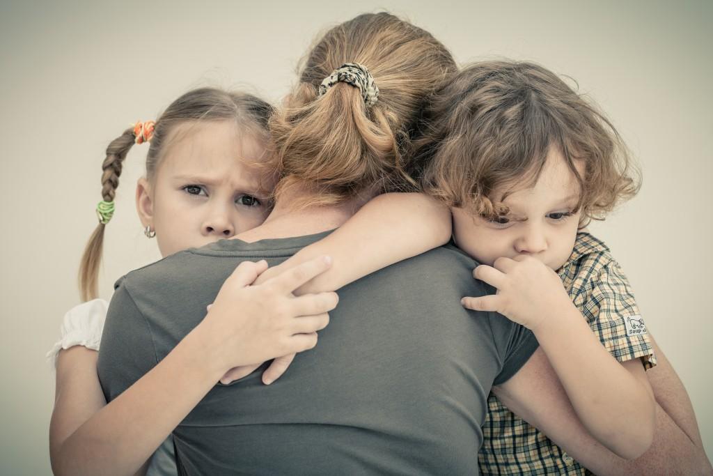 mother hugging children
