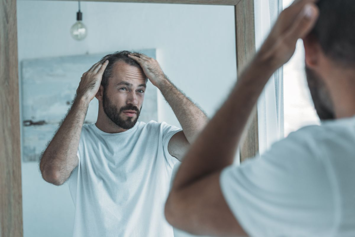 man looking at the mirror touching his hair