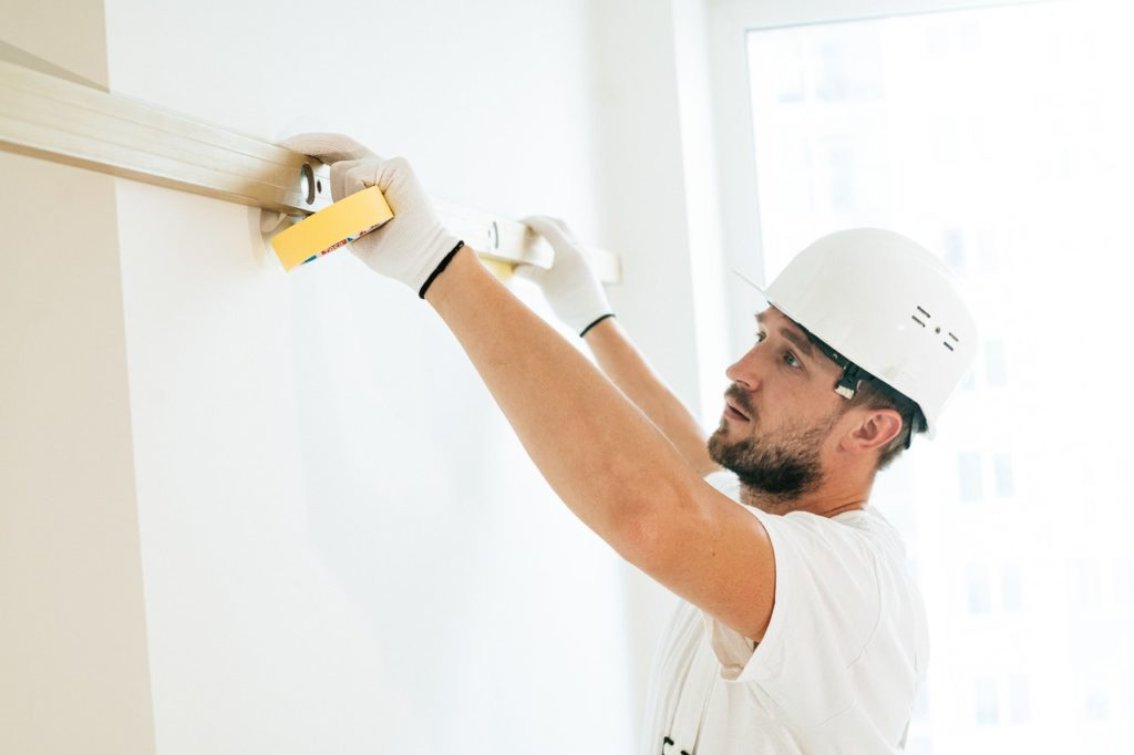 man measuring a wall