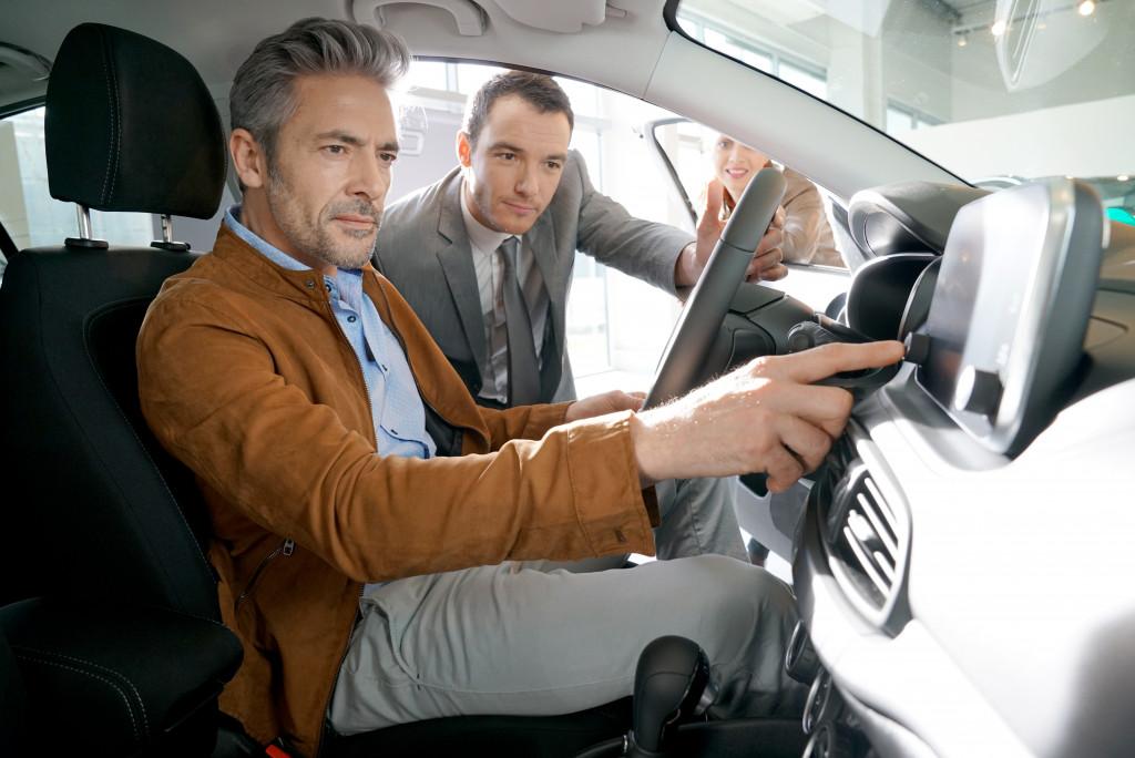 men looking at a car dashboard