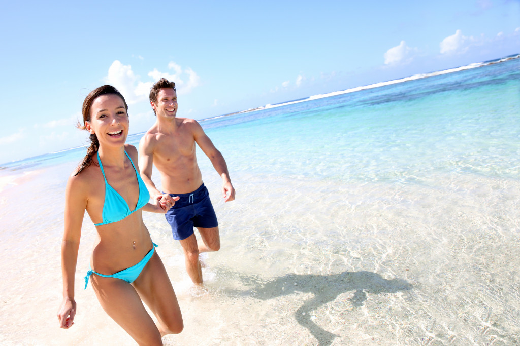 man and woman running in beach