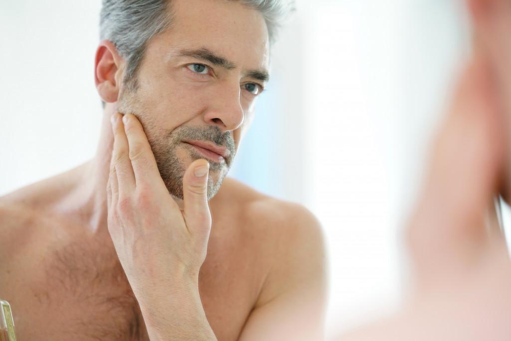 man facing a mirror touching his face