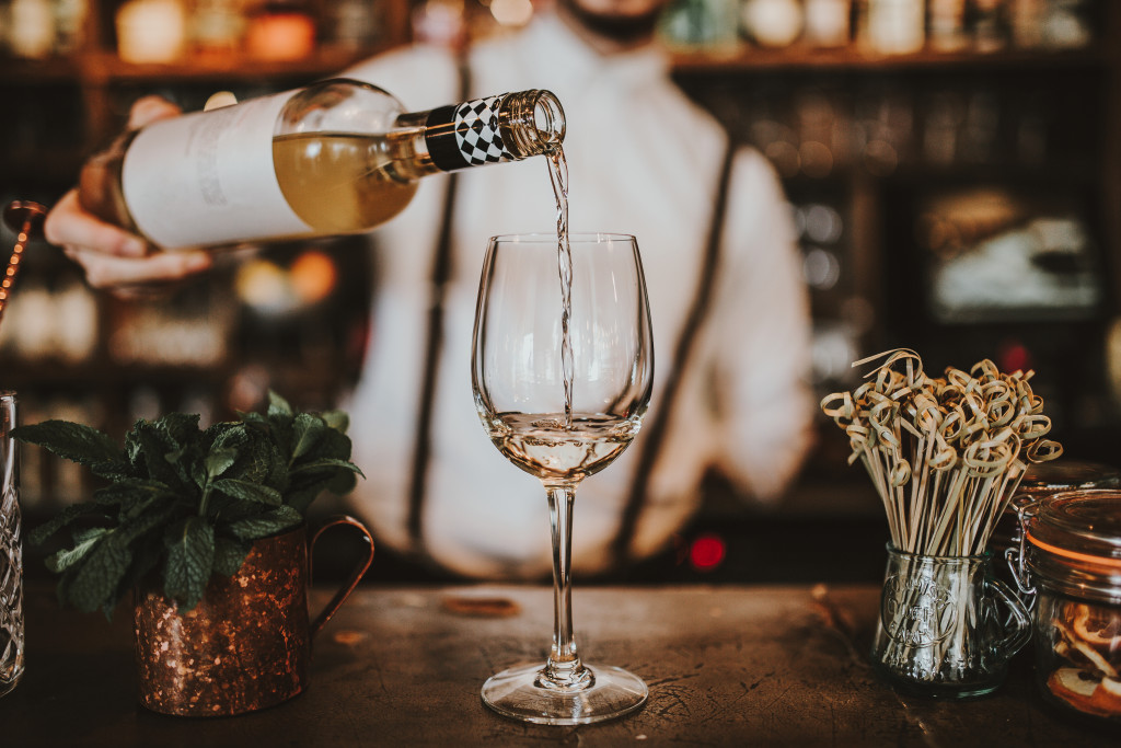 man pouring wine into a glass
